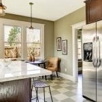 Olive tone kitchen room with steel refrigerator and marble top kitchen island